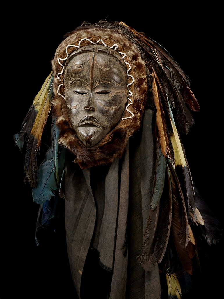 A mask with closed eyes and a slight frown.  In place of hair, the mask has many long and multi-colored feathers, and what appears to be a fur trim around the edges of the face.