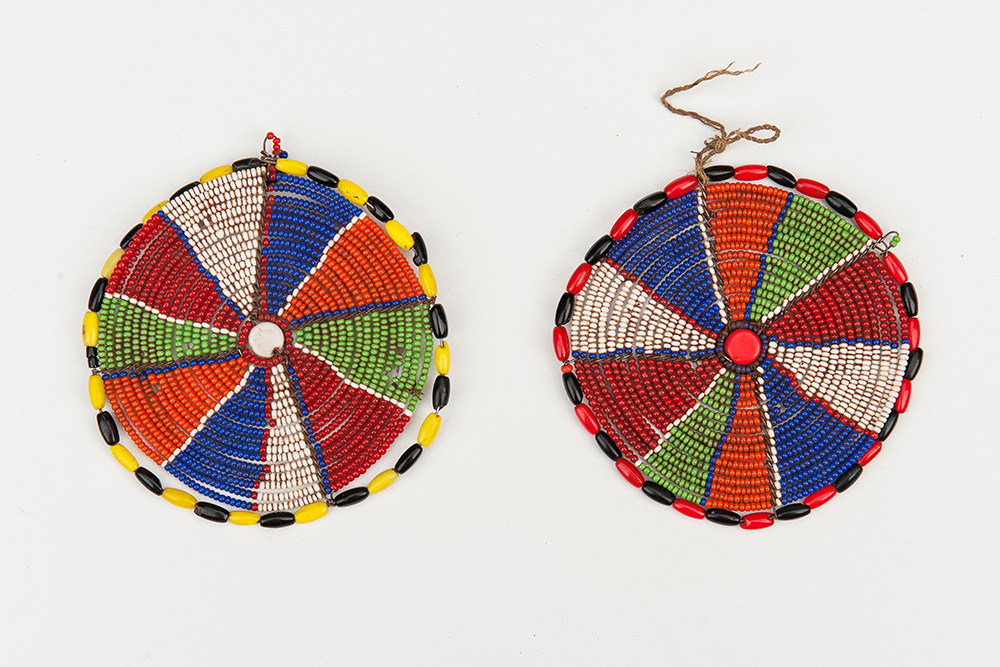Two flat discs made of beads.  Each disc is divided into slice-like segments of different colors, and bordered with two alternating colored beads.