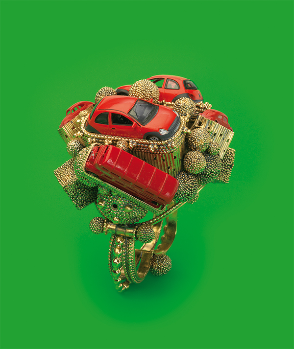 A sculpture of gold-tone pieces and red toy cars and buses, against a green background.